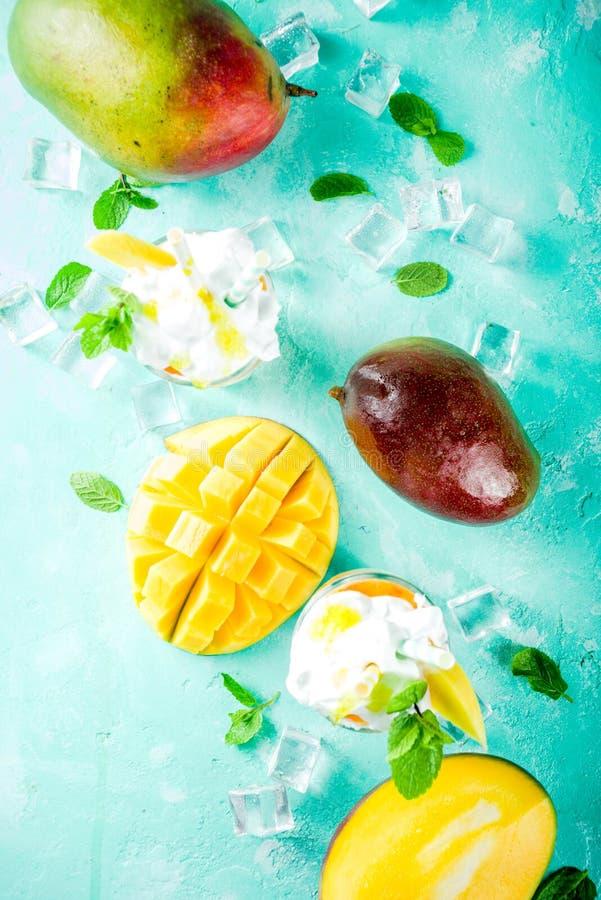 Tropical mango milkshake. Tropical sweet dessert drink. mango milkshake or smoothie cocktail, with mango slices, mint and ice cubes, light blue background copy stock photo