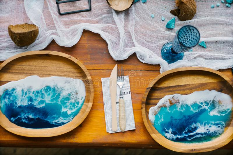 Tropical or marine style decor in the decoration of the festive table setting. Color of the year 2020, classic blue. Wooden plate stock photos