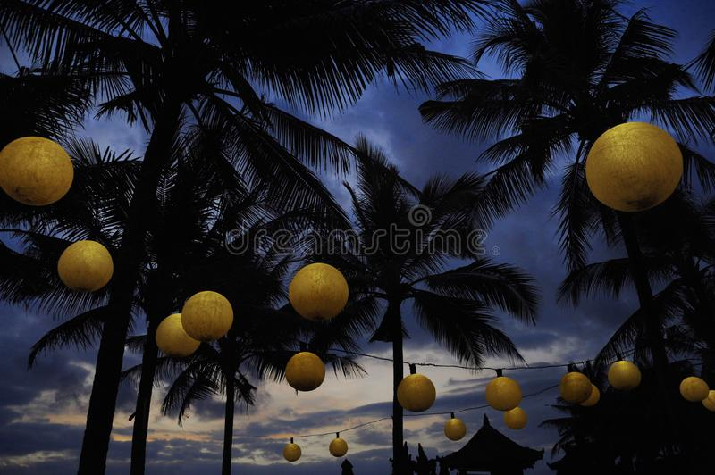 Tropical night landscape at luxury beach resort with a view of palm trees under a sunset sky with lamps and lantern lights deco in. Summer holidays travel royalty free stock image