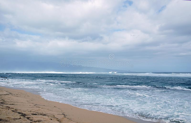 Tropical ocean meets mountain and cloudy blue skies royalty free stock photography