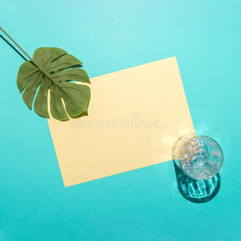 Tropical palm leaf with glass and ice cubes on bright blue background. Minimal summer composition. Flat lay royalty free stock photos