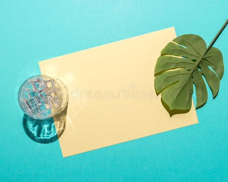 Tropical palm leaf with glass and ice cubes on bright blue background. Minimal summer composition. Flat lay stock photos