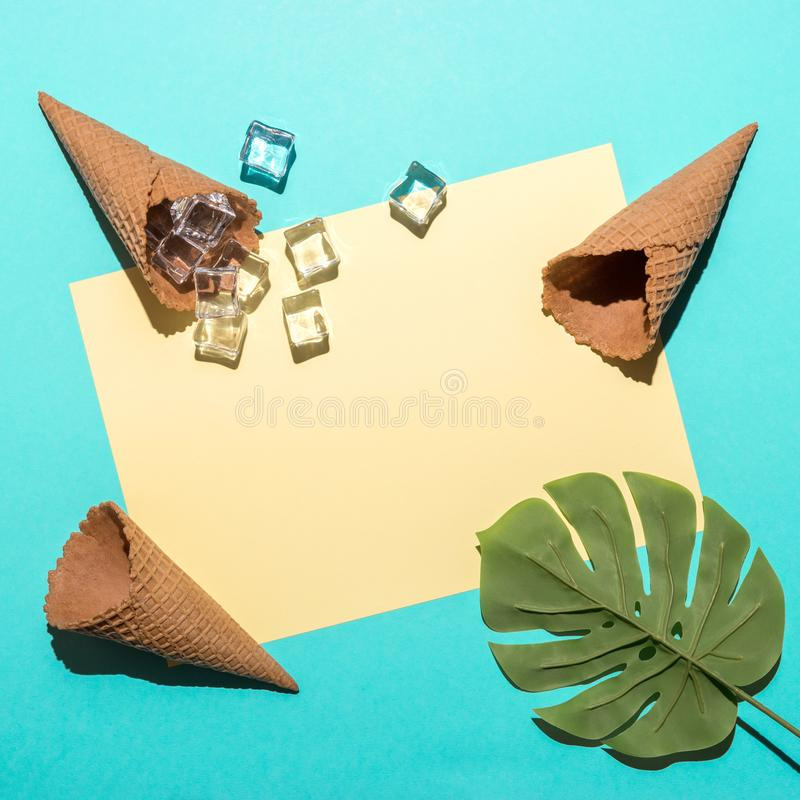Tropical palm leaf with  ice cubes and ice cream cones on bright blue background. Minimal summer composition. Flat lay stock photo