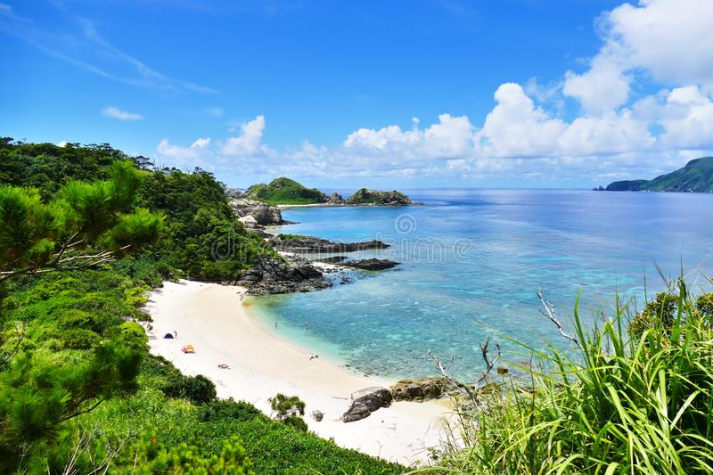 Tropical paradise of a pristine white beach, greenery, turquoise sea and deep blue sunny sky at Zamami, Okinawa, Japan royalty free stock image