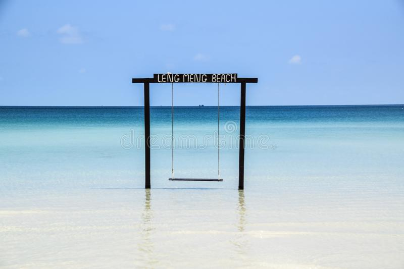 Tropical Paradise Swing over Crystal Clear Water, Leng Meng Beach, Cambodia royalty free stock image