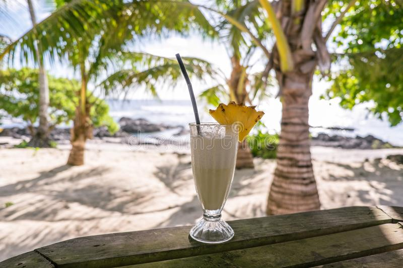Tropical pina colada cocktail drink with pineapple garnish in glass with straw at exotic beach at Lefaga, Upolu Island, Samoa, So royalty free stock image