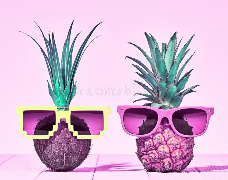 Tropical Pineapple and Coconut. Two Hipster Fruits. Tropical Pineapple and Coconut. Bright Summer Color. Two Hipster Fruits in Trendy Sunglasses. Fashion Style stock photos