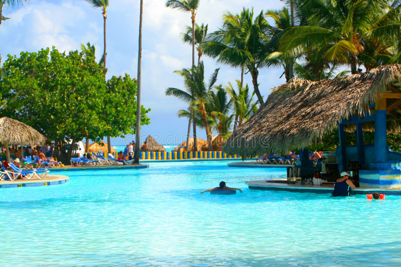 Tropical pool bar. With families enjoying their vacation at a Caribbean resort royalty free stock photo