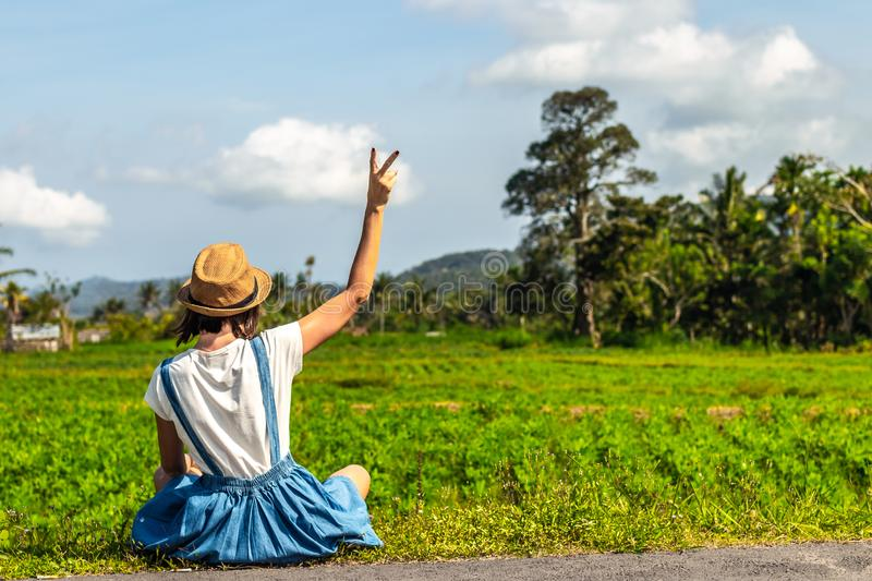 Tropical portrait of young happy woman with straw hat on a road with coconut palms and tropical trees. Bali island. stock photos
