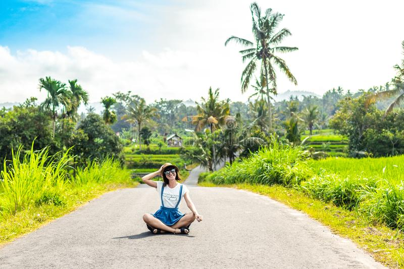 Tropical portrait of young happy woman with straw hat on a road with coconut palms and tropical trees. Bali island. royalty free stock images