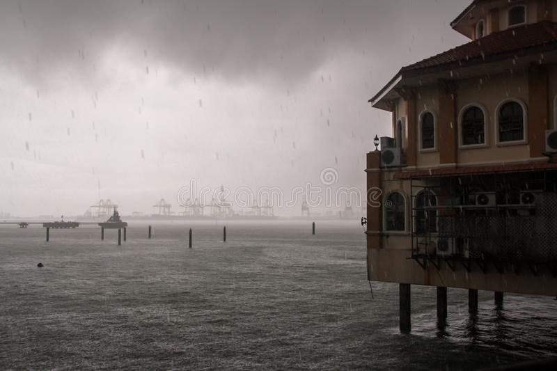 Tropical rain in the port of Georgetown. Malaysia. Black cloud and port cranes royalty free stock images
