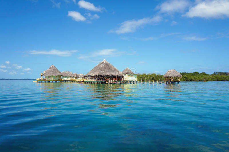 Tropical resort overwater with thatched roofs royalty free stock photos