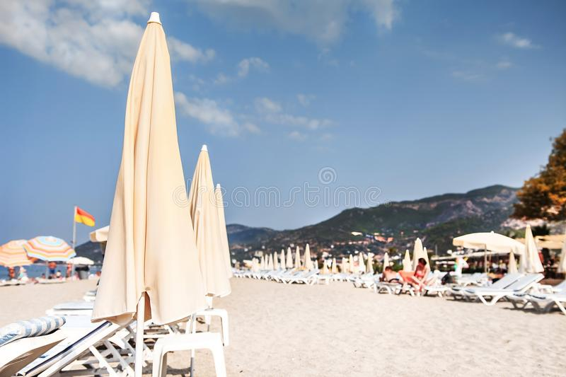 Tropical resort sandy beach soft selective focus. Beach with sun umbrellas and deck chair or sunbeds on bright clear day royalty free stock photos