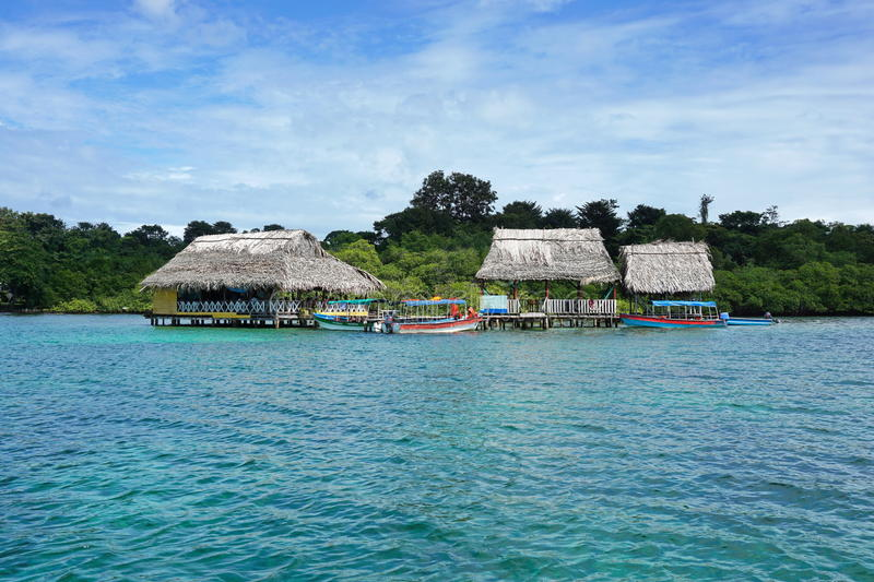 Tropical restaurant with thatched roof over water stock photography