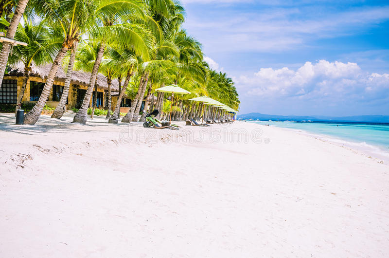 Tropical sandy beach at Panglao Bohol island with Sme Beach chairs under palm trees. Travel Vacation. Philippines.  royalty free stock image