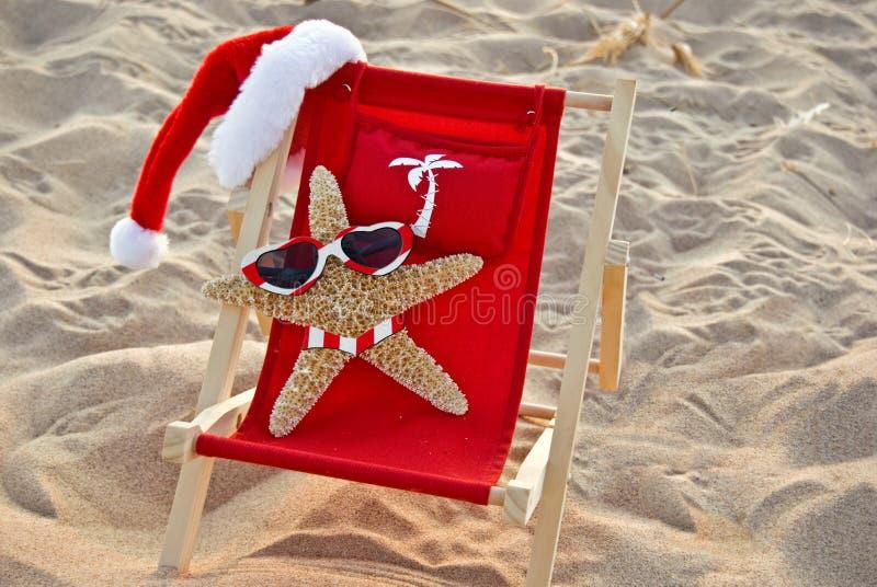 Santa Starfish on a red beach chair royalty free stock photo