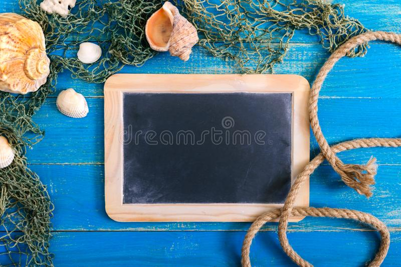 Tropical sea background. Different shells, old fishing net on the blue boards, top view. Free space for inscriptions on the slate. Summer theme royalty free stock photography