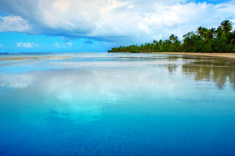 Tropical sea and blue sky background. Big clouds are reflected in the water. royalty free stock photography