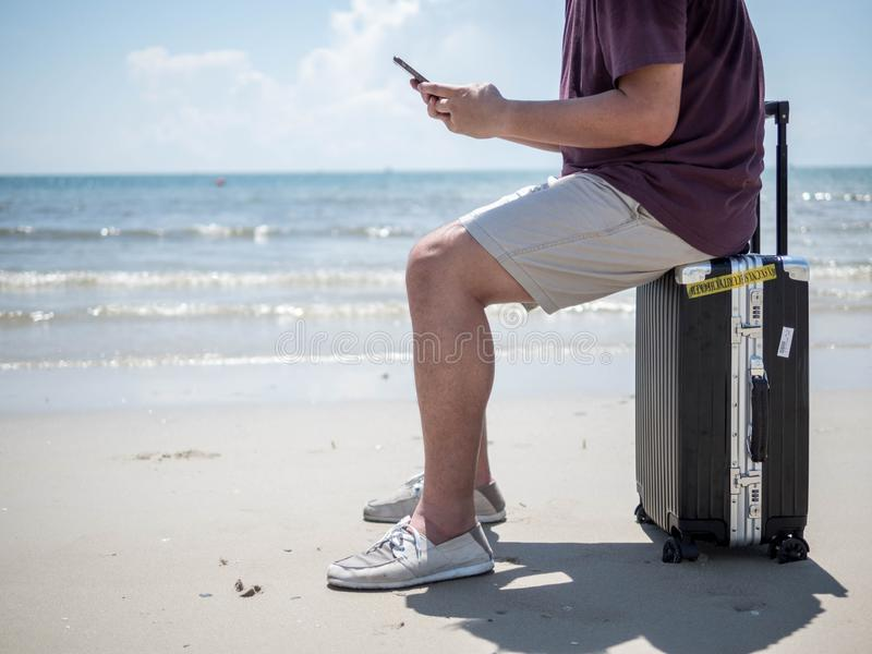 Tropical sea, Young man sitting on Travel suitcase and using smart phone at the beach. Summer holiday traveling concept design stock image