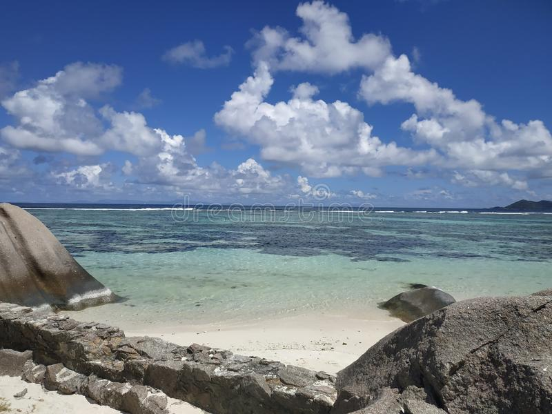 Tropical shore at Ladigue Seychelles with clouds and light blue transparent water stock images