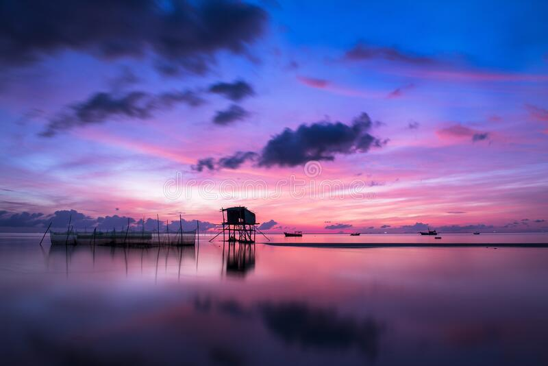 Tropical stilt houses in sea at sunset stock image
