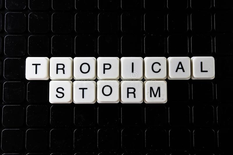 Tropical storm white text word on black cover. Text word crossword. Alphabet letter blocks game texture background. Storm royalty free stock image
