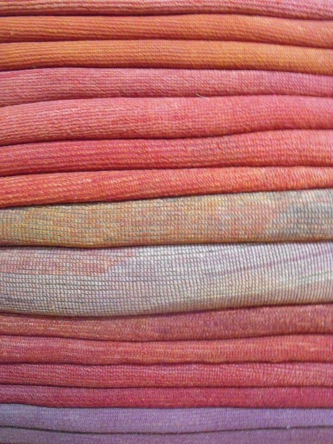 Stack of wool fabrics detail in orange pink purple violet stock images