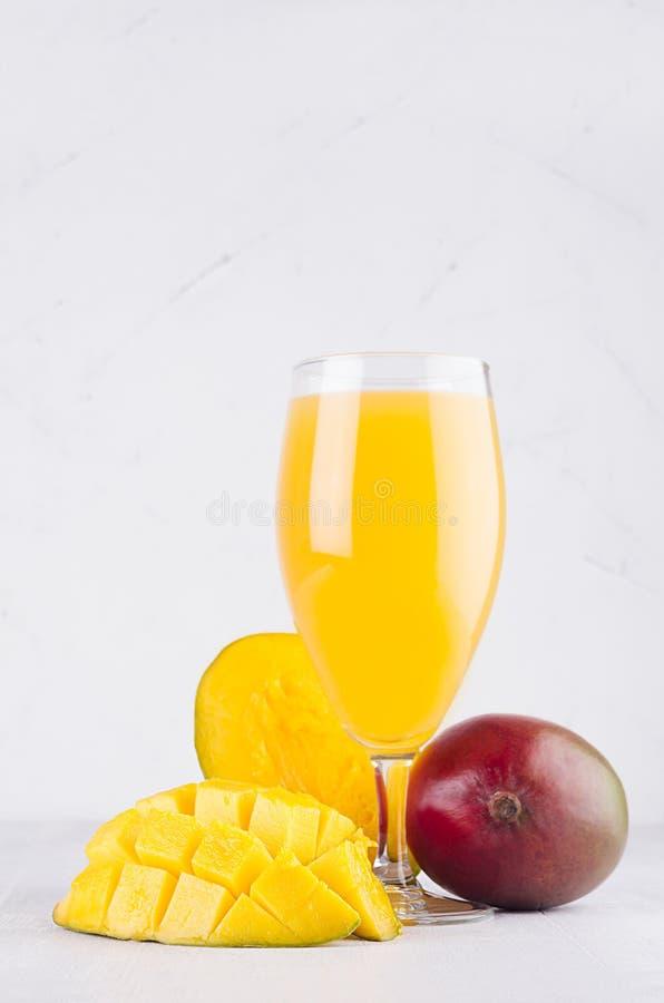 Tropical summer juice of ripe fresh mango with pulpy chopped slice on soft light elegant white background, vertical. Tropical summer juice of ripe fresh mango stock images