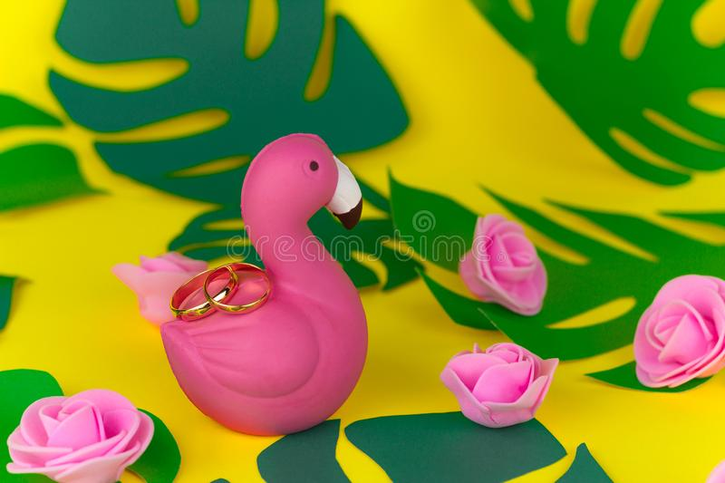 Tropical wedding decorations,gold rings on flamingos, tropical leaves and flowers royalty free stock photos