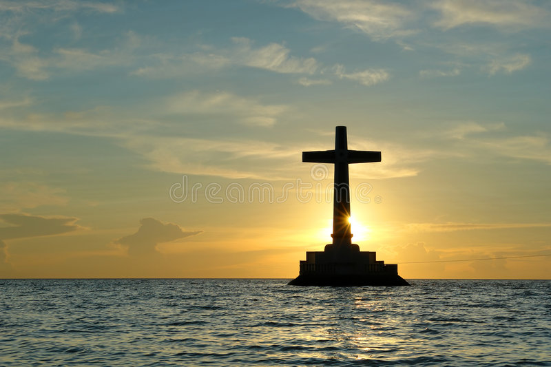 Tropical sunset with cross silhouette. royalty free stock photo
