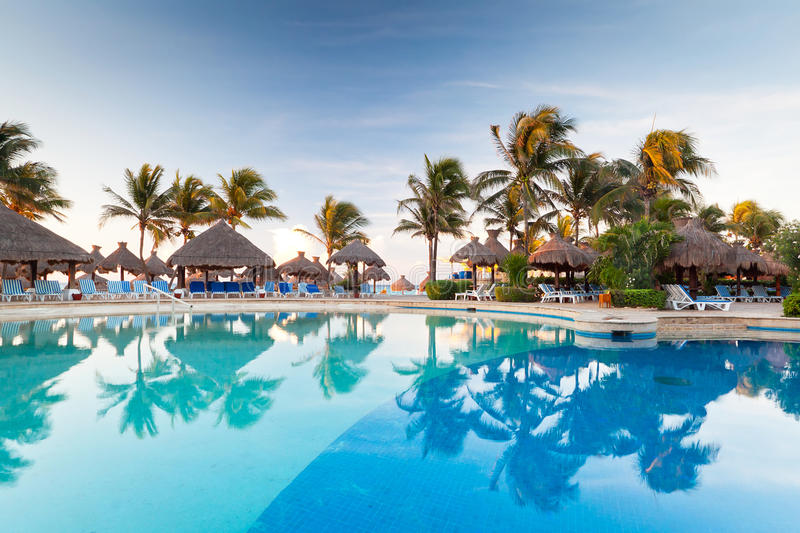 Tropical swimming pool at sunrise stock images