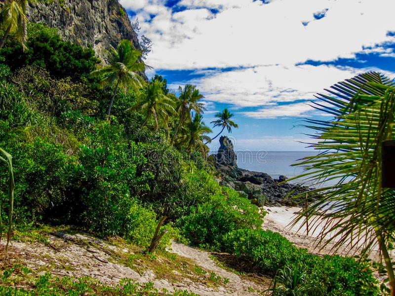 Tropical trail end surprise beach. Puffy white clouds over mountain falling into the blue sea spotted as you step out of the tropical forest and onto a sandy royalty free stock photography