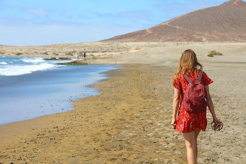 Tropical traveling. Young woman with red dress and backpack walking barefoot by sea beach enjoying landscape royalty free stock images