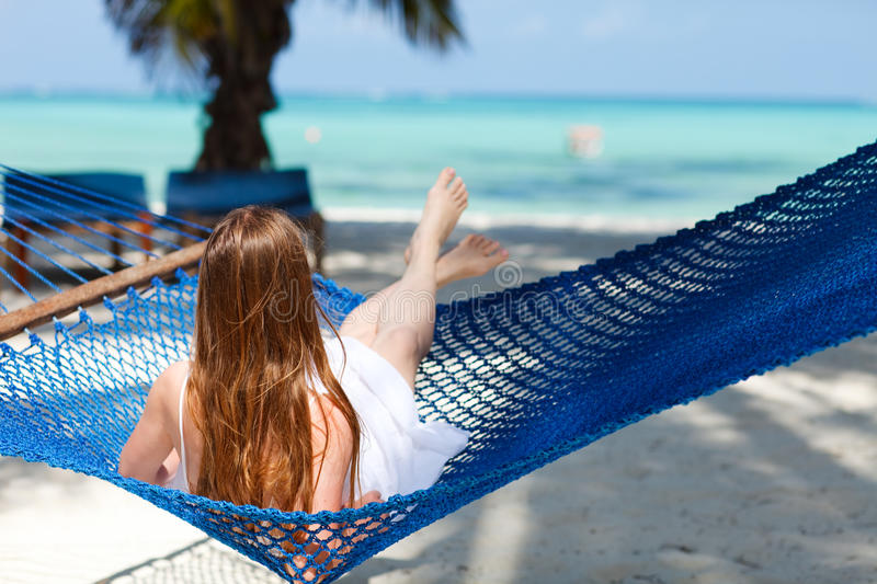 Tropical vacation. Beautiful woman relaxing in hammock on tropical beach of Zanzibar island royalty free stock photography