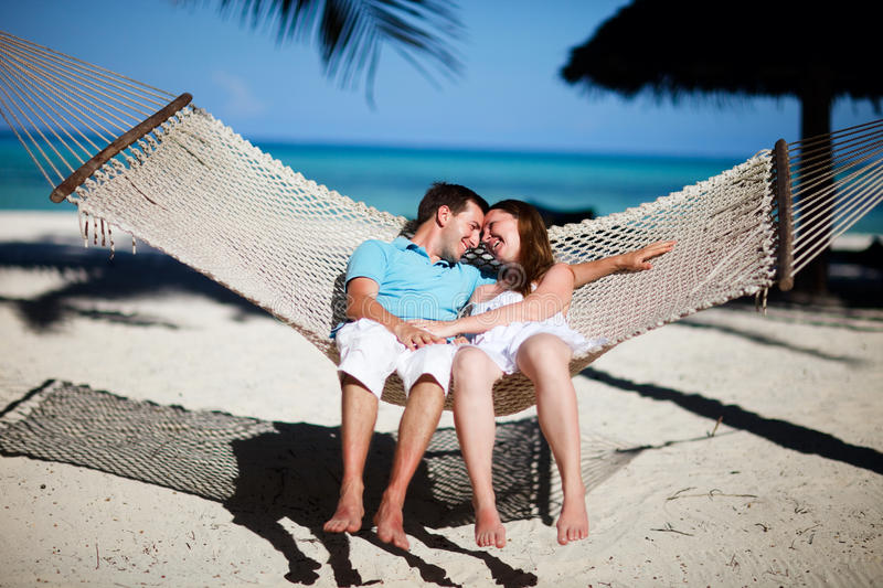 Tropical vacation. Young romantic couple relaxing in hammock on tropical beach of Zanzibar island royalty free stock images