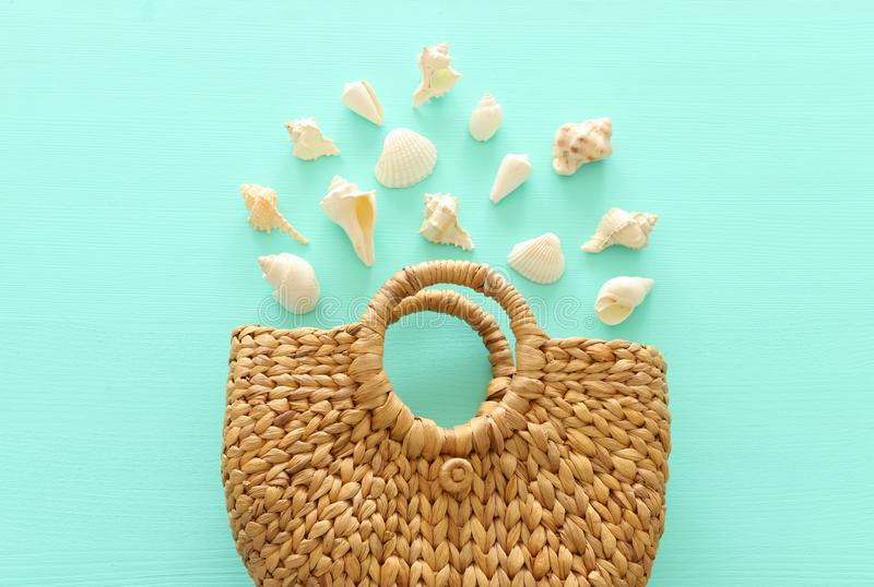 Tropical vacation and summer travel concept with wicker beach bag and seashells over pastel mint blue background. Top view royalty free stock photo