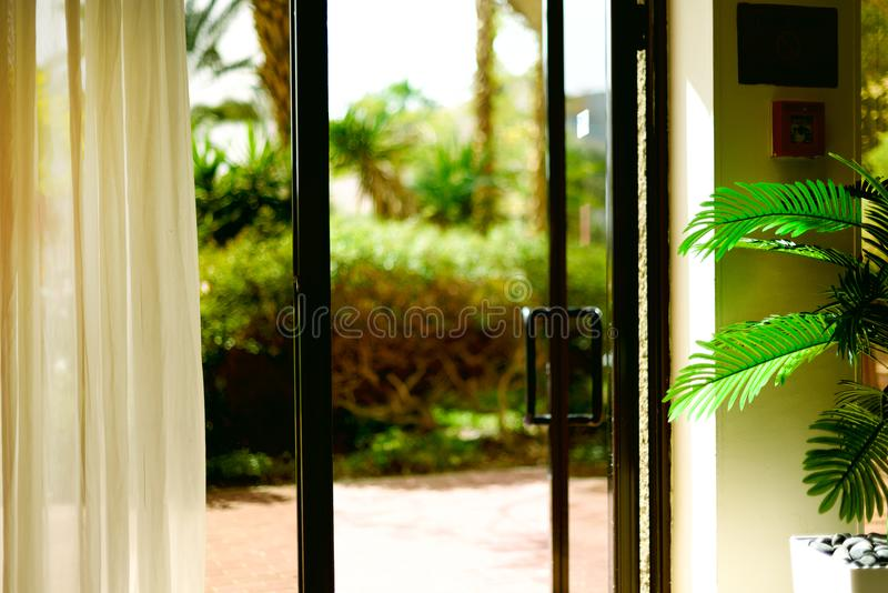 Tropical view background. Summer, travel, vacation and holiday concept. Open window, door and white curtain with blurred. Palm garden view from hotel. Exotic stock images