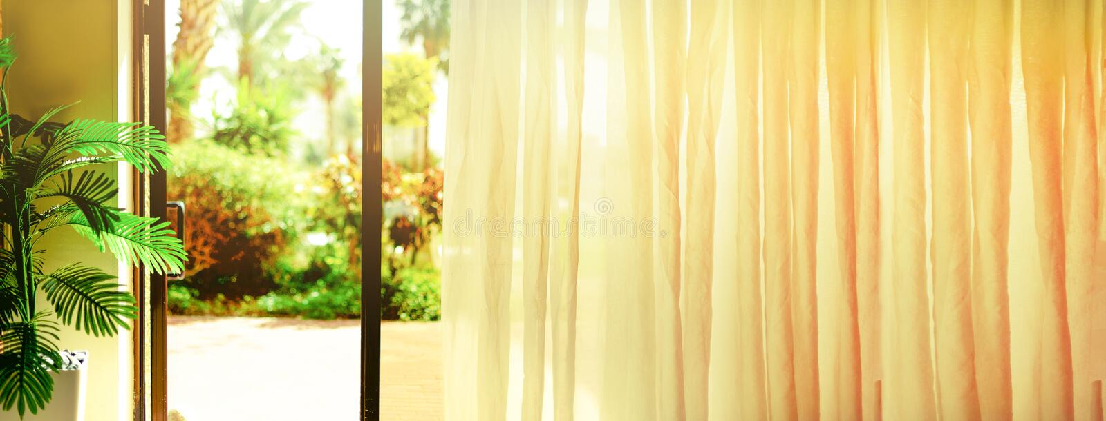 Tropical view background. Summer, travel, vacation and holiday concept. Open window, door and white curtain with blurred. Palm garden view from hotel. Exotic royalty free stock photo