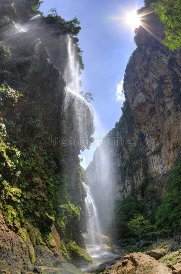 Tropical waterfall in canyon. HDR image of beautiful El Aguacero waterfall in Chiapas, Mexico pouring into deep canyon with sun shining above stock photos
