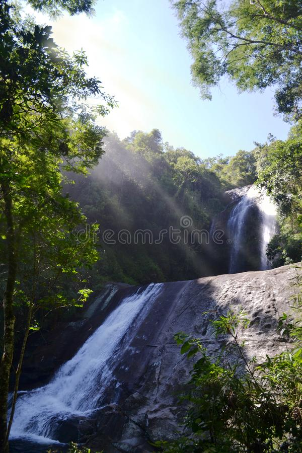 Tropical waterfall and sunray. Tropical waterfall with a totem and sunray in Petropolis, Rio de Janeiro, Brazil stock images