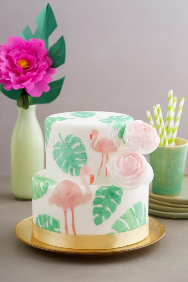 Tropical wedding cake. Two tiered tropical wedding cake with fondant, tropical wafer paper leaves and flamingos with ranunculus flowers on golden cale platter stock photo