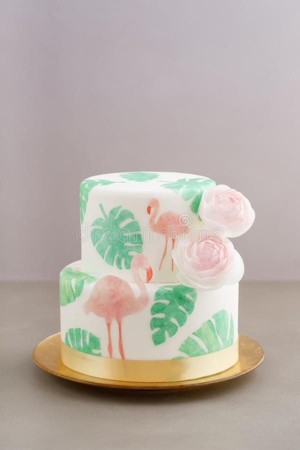 Tropical wedding cake. Two tiered tropical wedding cake with fondant, tropical wafer paper leaves and flamingos with ranunculus flowers on golden cale platter royalty free stock photography
