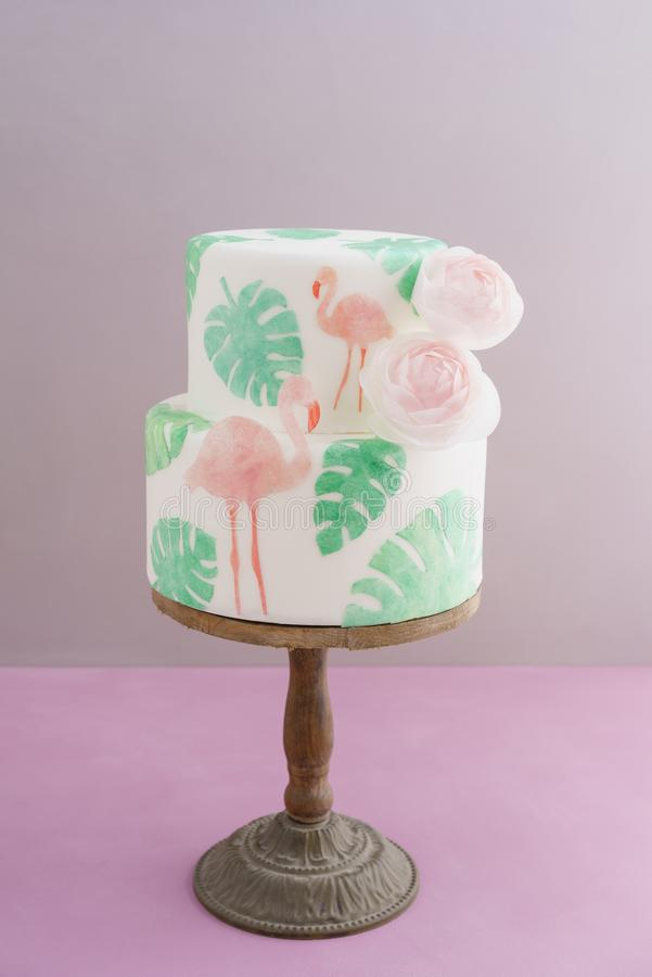 Tropical wedding cake. Two tiered tropical wedding cake with fondant, tropical wafer paper leaves and flamingos with ranunculus flowers on wooden cake stand stock images