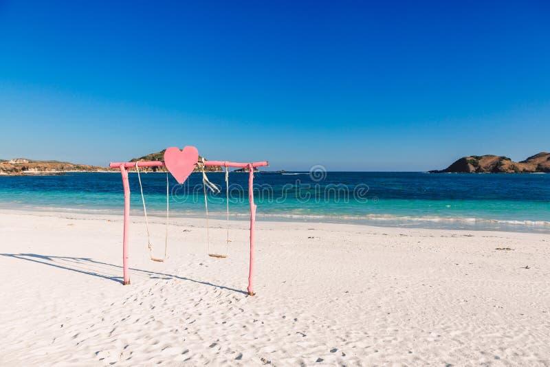 Tropikalna biała piasek plaża z błękitnym oceanem i menchie huśtamy się obraz royalty free