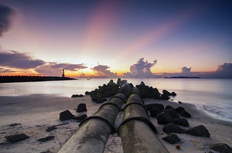 Tropikalna plaża nad wschodu słońca tłem chmury i światło słoneczne promień na horyzoncie zdjęcie stock