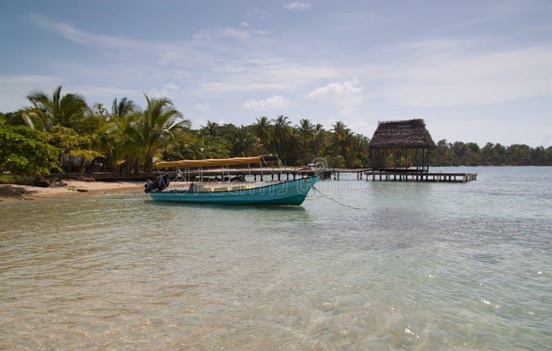 Tropikalna plaża z łodzią i dokiem obraz stock