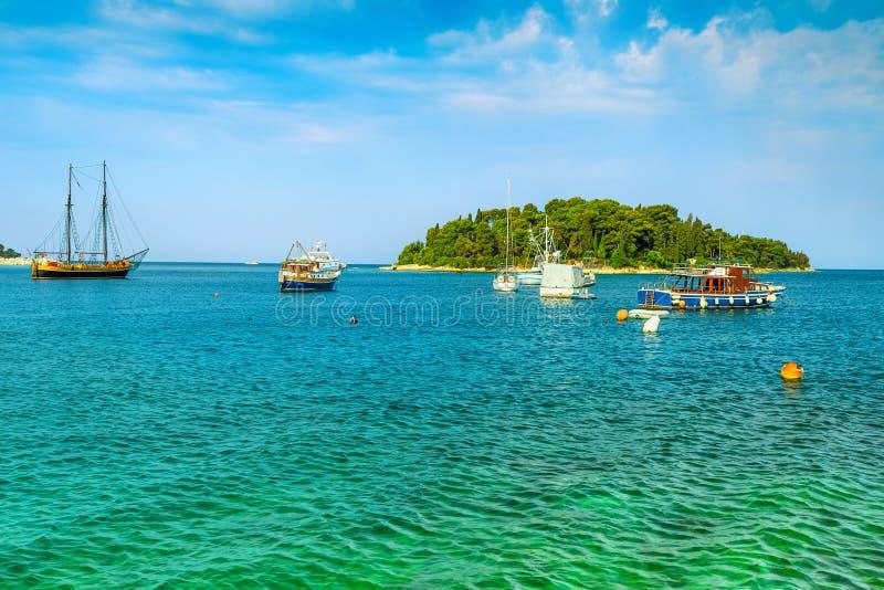 Tropikalna zielona wyspa i łodzie na morzu blisko Rovinj, obrazy stock