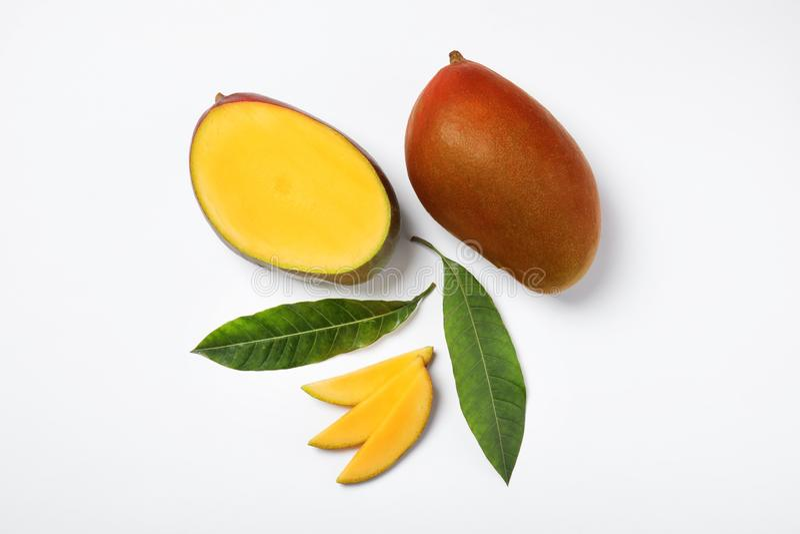 Tropikalny cięcie i cały mango z zieleń liśćmi odizolowywającymi na bielu zdjęcia stock