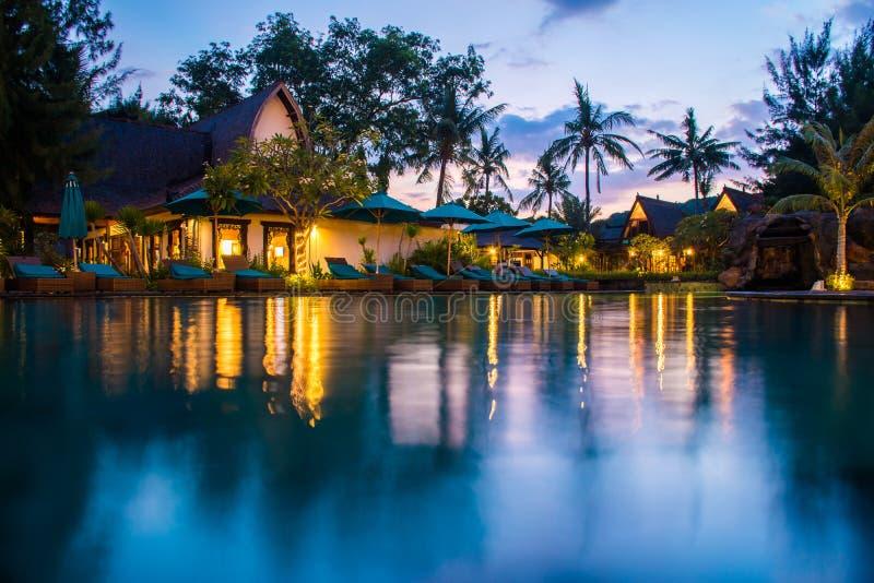 Tropikalny hotel z pływackim basenem przy nocą z odbiciami i palmami, Gil Trawangan, Lombok, Indonezja fotografia royalty free