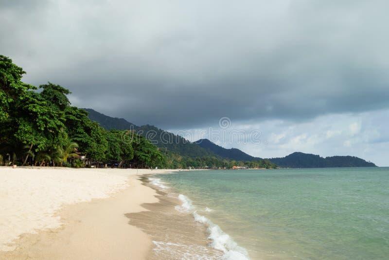 Tropikalny krajobraz z błękitnym morzem, piaskowatą plażą, drzewkami palmowymi i chmurnym niebem w pogodzie sztormowej, obrazy royalty free